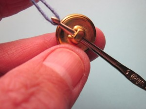 Pulling a loop of yarn through the button shank