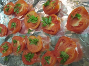 Halved tomatoes sprinkled with seasoning and chopped basil