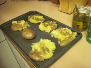 Whole cooked red potatoes on baking tray - before and after smashing
